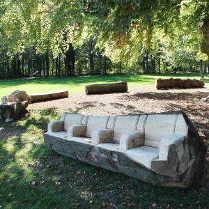 boomzaagkunstenaar maakt zitbanken park van Schoten kasteel
